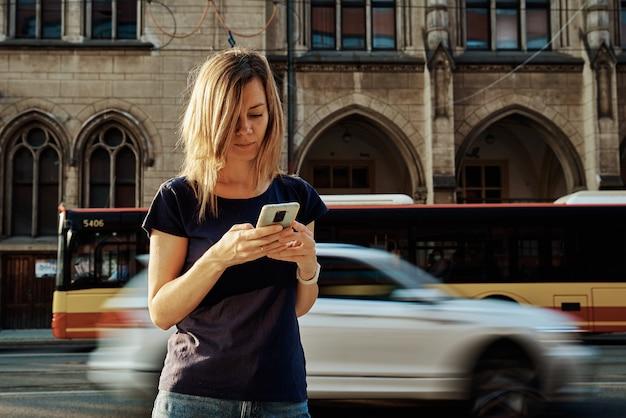 Женщина с помощью смартфона на городской улице