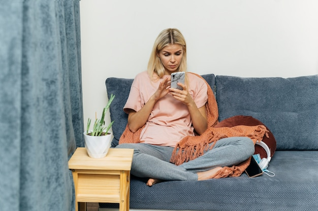 Женщина, использующая смартфон дома во время пандемии