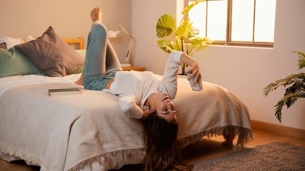 ベッドで自宅でスマートフォンを使用している女性
