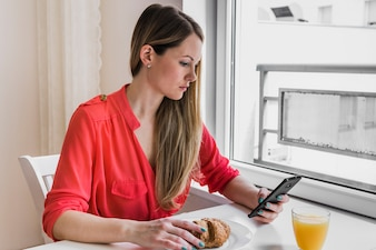 Woman using smartphone during breakfast