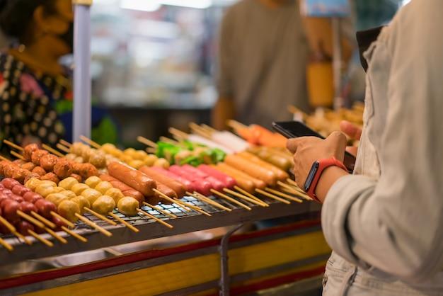 夜のアジアで屋台の食べ物の支払いにスマートフォンを使用している女性