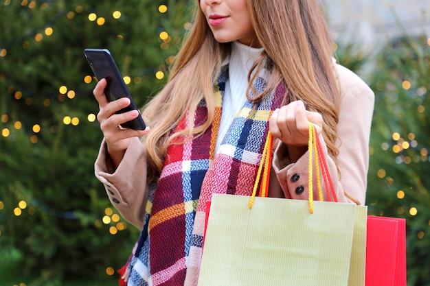 オンラインショッピングやクリスマスの時期にバッグを運ぶためにスマートフォンを使用している女性