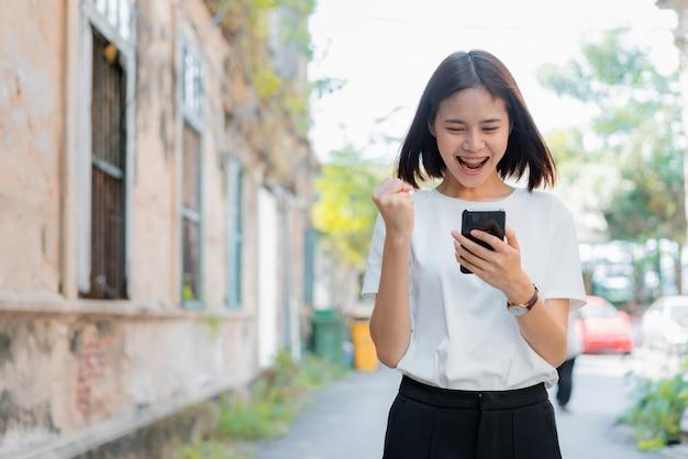 アプリケーションのためのスマートフォンを使用して、幸せなジェスチャーを示す女性。