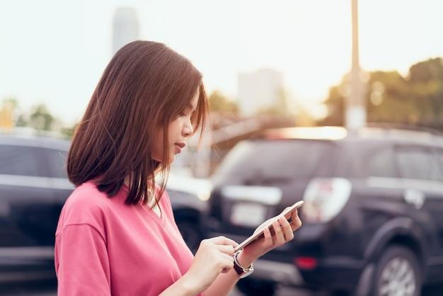 Женщина, используя смартфон для приложения на фоне размытия автомобиля.