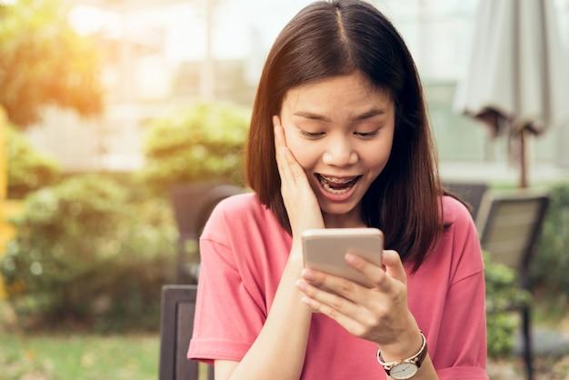 公園のカフェでテーブルの上のアプリケーションにスマートフォンを使用しての女性。