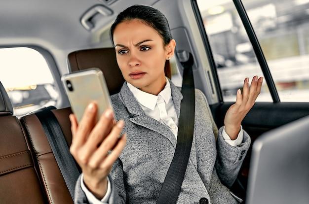불쾌한 표정, 여자 작업 개념으로 차에서 일하기 위해 스마트 폰을 사용하는 여자.