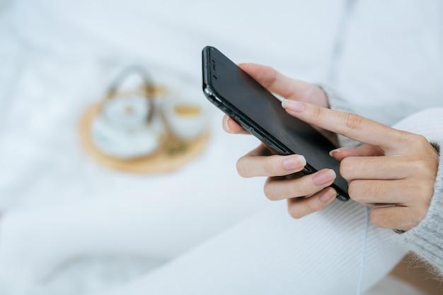 Donna che utilizza smartphone sul suo letto in una giornata fredda