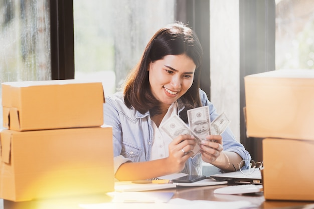 Woman using smartphone and holding money banknotes smiles with happy.