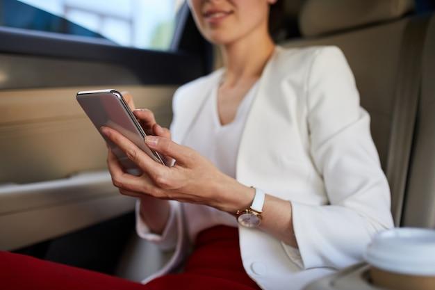 車の中でスマートフォンを使用して女性