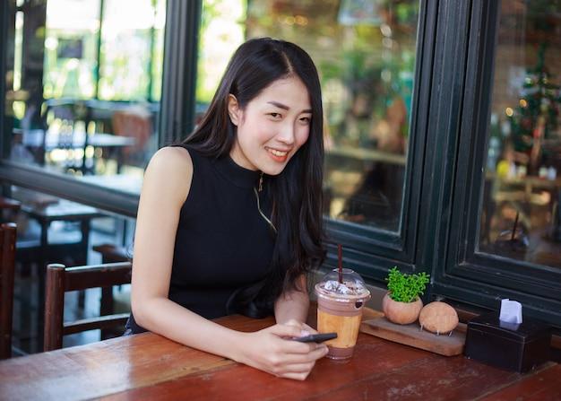 カフェでスマートフォンを使っている女性
