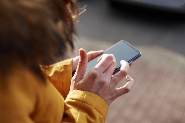Женщина используя smartphone в городе внешнем, конец вверх. женские руки, набрав сообщение на мобильном телефоне