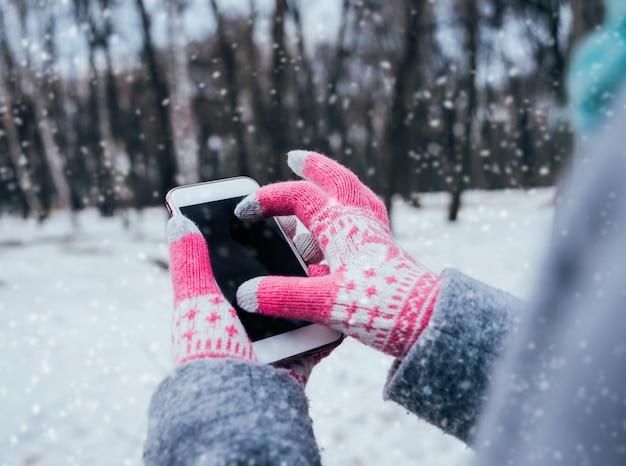 터치 스크린 장갑 겨울에 스마트 폰을 사용하는 여자