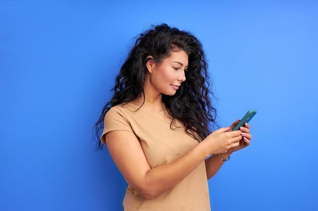 スマートフォンを使用して、画面を見て、メッセージを入力し、孤立した肖像画を使用している女性。側面図