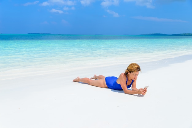 Woman using smartphone relaxing on white sand beach