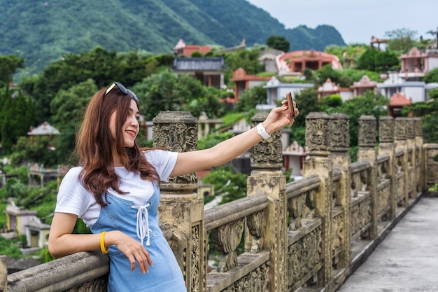 Woman using smartphone to selfie photo in jiufen, taiwan