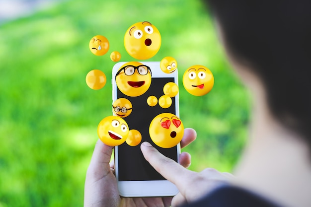 Woman using smartphone sending emojis