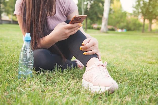 公園の芝生の上に座ってスマートフォンを使用している女性。