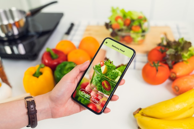 Woman using smartphone and touching application screen for ordering salad online on table at the kitchen.