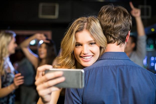 Woman using smartphone while hugging boyfriend
