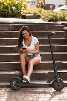 Woman using smartphone while sitting on steps next to scooter