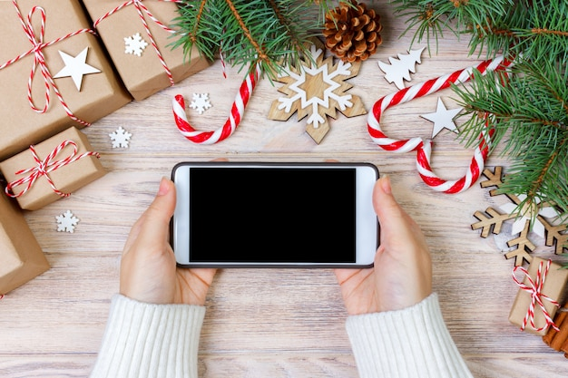 Woman using smartphone with blank screen, festive trumpery frame, christmas gift search, online shopping, seasonal discounts and sale concept