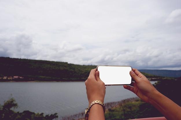 Женщина, использующая смартфон с пустым экраном на природе