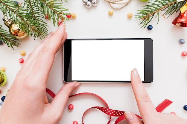 クリスマスの装飾とテーブルの上の空白の画面でスマートフォンを使用して女性