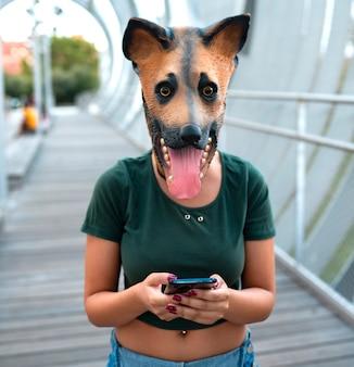 Женщина с помощью смартфона в маске собаки
