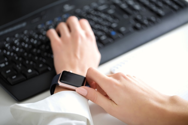 Woman using  smartwatch and working on  keyboard  in  office