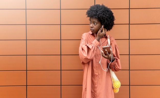Woman using some earphones while holding her smartphone