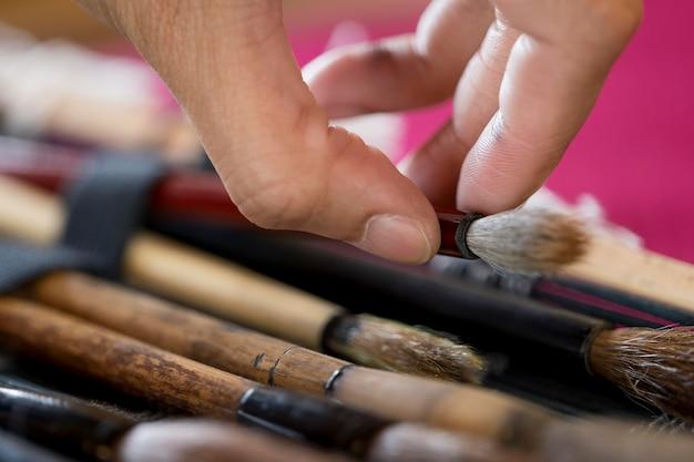 日本の芸術のために特別なブラシを使用している女性