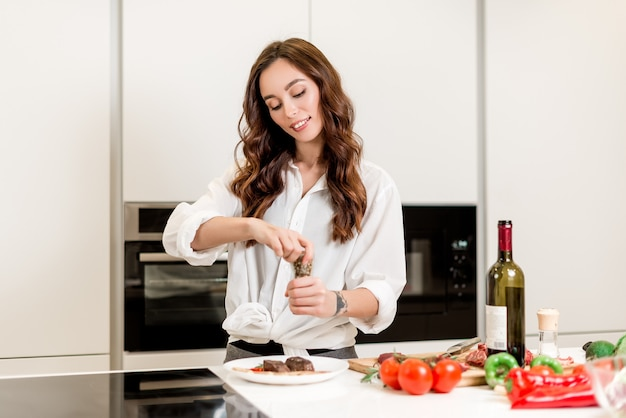 Woman using spices on the meat she cooked at the kitchen