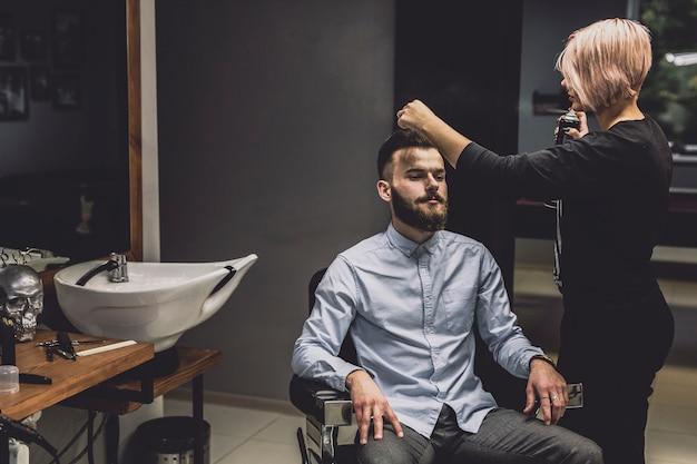 Женщина, использующая спрей на клиента в парикмахерской