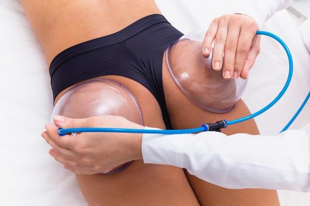 그녀의 엉덩이에 흡입 컵 펌프를 사용하여 들어 올리는 여성.