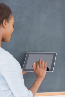 Woman using a tablet computer next to a blackboard