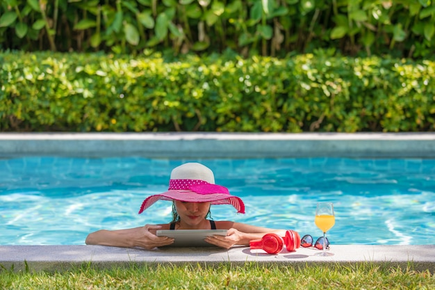 Woman using tablet computer in pool