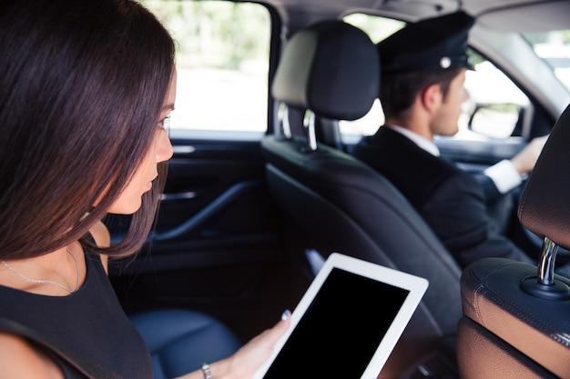 Женщина с помощью планшетного компьютера во время езды в такси