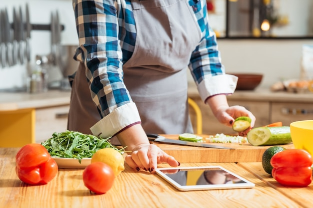 부엌에서 요리하는 동안 조리법을 확인하기 위해 태블릿을 사용하는 여자