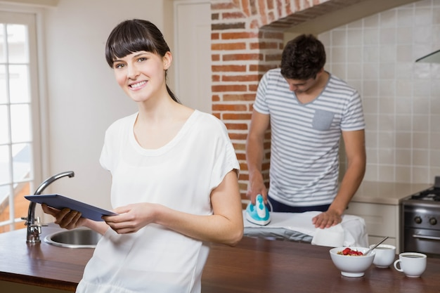 Woman using tablet in kitchen while man ironing a shirt