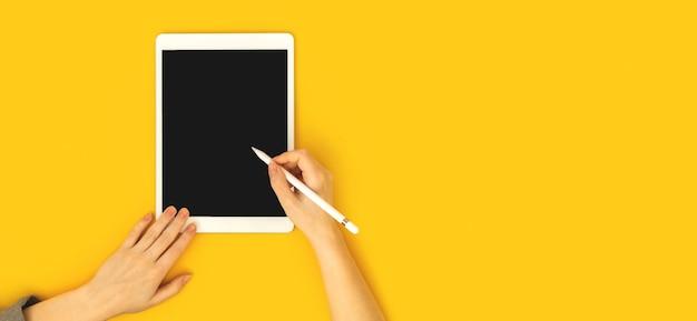 タブレットのモックアップ、スタイラス鉛筆、黄色の背景、警官スペース写真、教育コンセプトバナーとカラフルなオフィスワークスペースを使用して女性