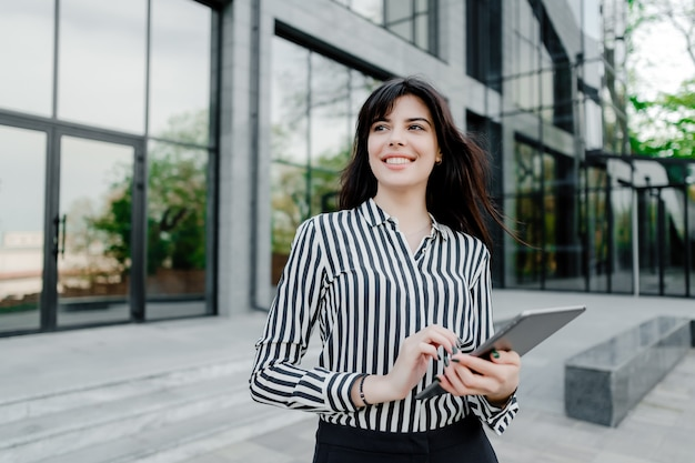 Woman using tablet outside company building