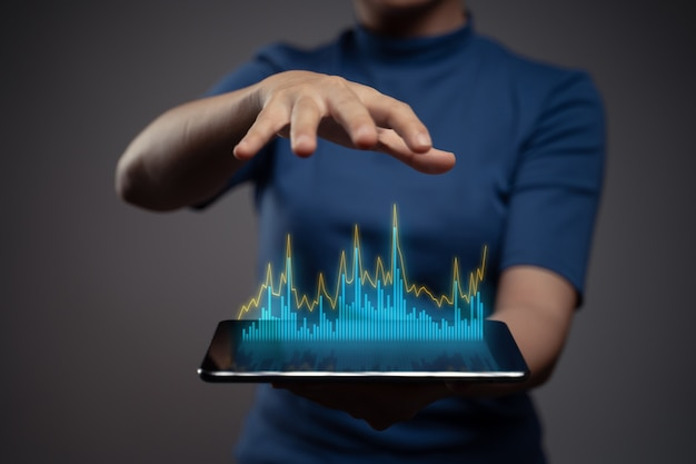 Woman using tablet planning digital marketing with chart hologram effect