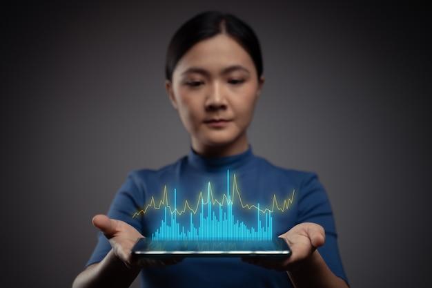 Женщина с помощью планшета, планирующего цифровой маркетинг с эффектом диаграммы голограммы