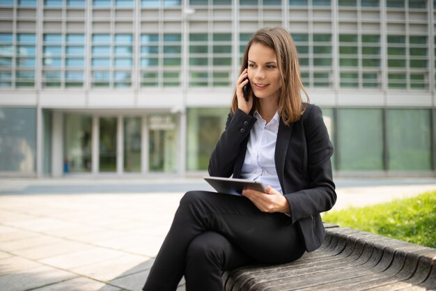 Woman using a tablet while talking on her mobile cell phone in front of her office