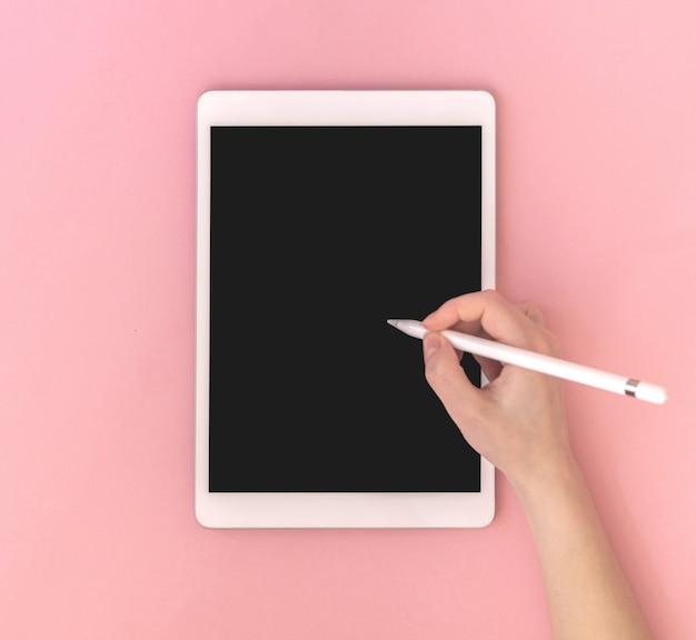 空白の画面、上面図、ピンクのカラフルな背景写真とスタイラスモックアップとタブレットを使用している女性