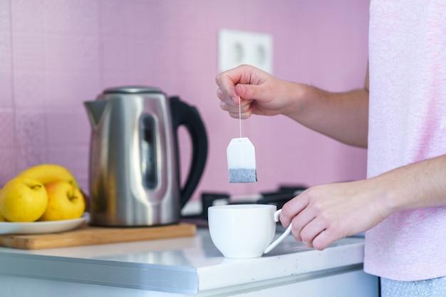 Женщина использует пакетик чая и электрический чайник для приготовления горячего чая дома на кухне