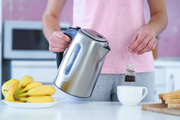 Woman using tea bag and electric kettle for brewing black tea at home at kitchen