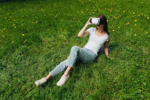 야외에서 봄 꽃밭에 누워 가상 현실 헤드셋을 사용하는 여자