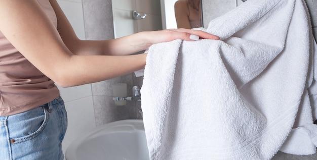 여자 화장실에서 손을 닦아 수건을 사용합니다.
