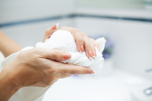 Woman using towel for wiping hands dry after washing